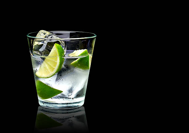 Vodka with lime and ice Vodka lime with ice in rocks glass on black background including clipping path vodka stock pictures, royalty-free photos & images