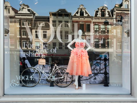 Amsterdam, The Netherlands - March 24, 2012: Vogue Fashion window display in Bijenkorf department store in Amsterdam. Mannequin with dress and bicycle in the window, behind the reflection of old traditional Dutch row houses from across the street.