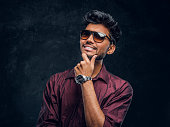 Vogue, fashion, style. Cheerful young Indian guy wearing a stylish shirt and sunglasses posing with hand on chin. Studio photo against a dark textured wall