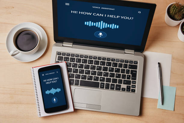 Voice assistant concept on laptop and smartphone screen stock photo
