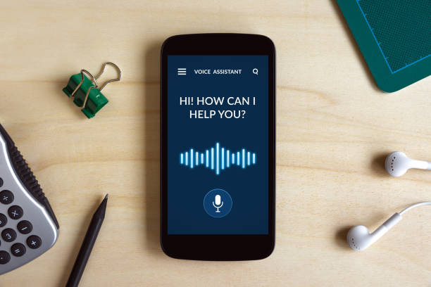 Voice assistant concept on smart phone screen on wooden desk stock photo