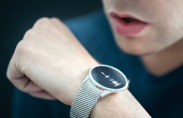 Voice recording or speech recognition technology in smart watch. Man talking to smartwatch mic and recorder. Personal assistant app to give command or send message. stock photo