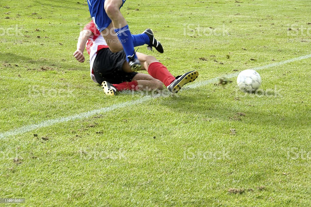 Voilent soccer tackle makes football player fall stock photo