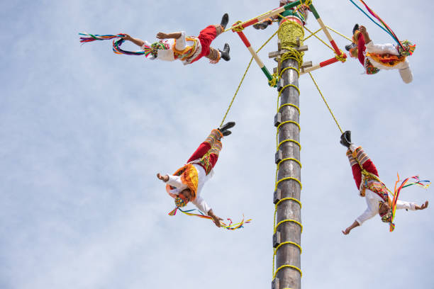 Voladores performing flying men show. Cancun, Mexico - Mar 15, 2017: Traditional flying birdmen performance by voladores: performers throw themselves off a tall wooden pole while rotating towards the ground as part of a ritual ceremony to ask for fertility. veracruz stock pictures, royalty-free photos & images