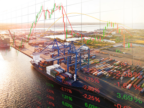 Volatile market stock data: overlay of mostly red changing numbers and bearish graph with container ship and cargo containers. This theme goes hand in hand with the global impact of the coronavirus covid-19 on the global economy and trade