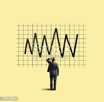 A businessman places his hand on his head as he looks up at a financial chart that shows the volatility of the financial markets.
