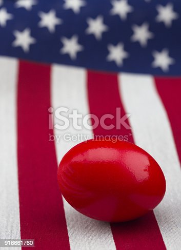 Danger and riskin the American stock and investment markets are reflected in vertical flag with red nest egg in foreground