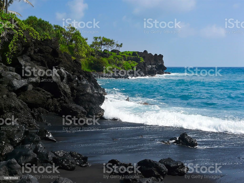 Volcanic black sand beach on Hawaii stock photo