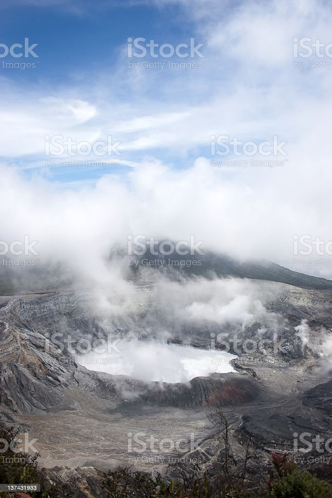 Volcanic crater with blue skies and vapour stock photo