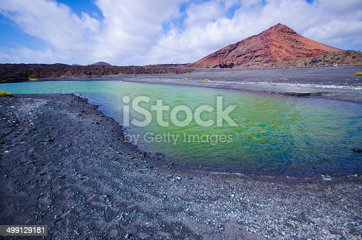 istock Volcanic lake with volcano at background 499129181