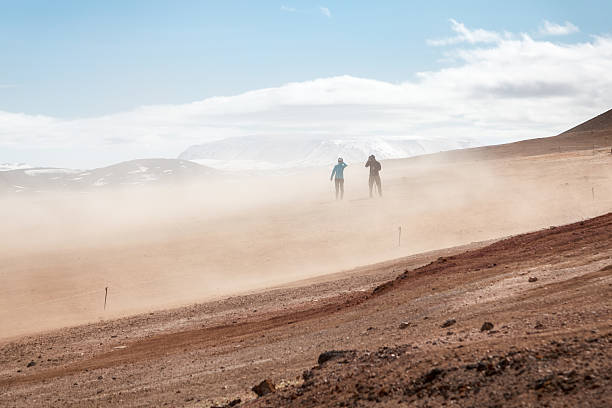 Volcanic landscape at Namaskard, Iceland Namaskard, Iceland - May 25, 2016: Two tourists in a sandstorm at Namaskard geothermal area i North Iceland namaskard geothermal area stock pictures, royalty-free photos & images