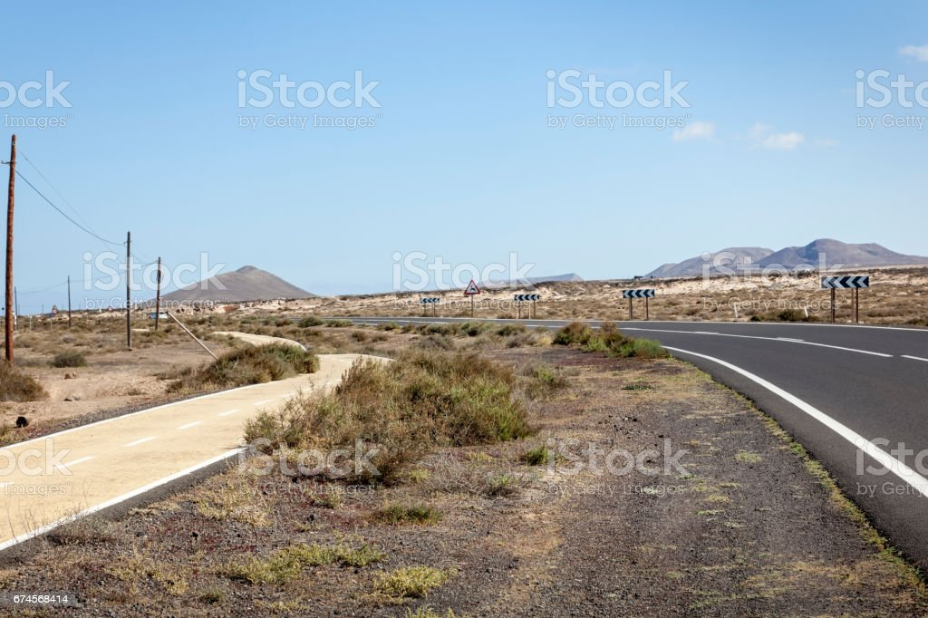 Volcanic landscape with road and bikepath stock photo