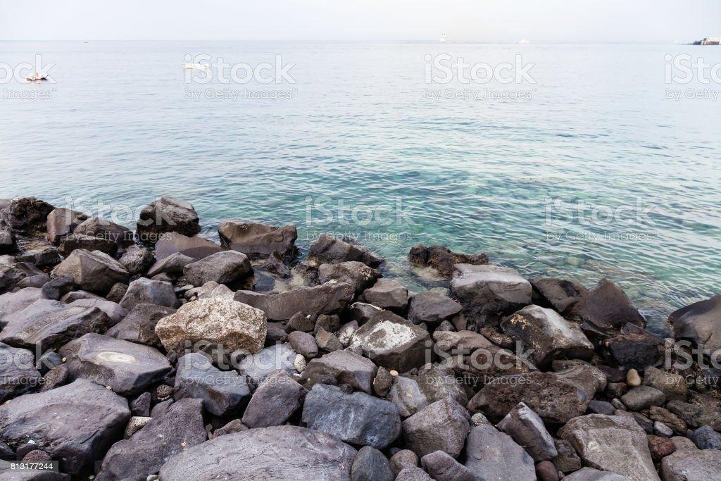 volcanic rocks on waterfront of Giardini Naxos stock photo