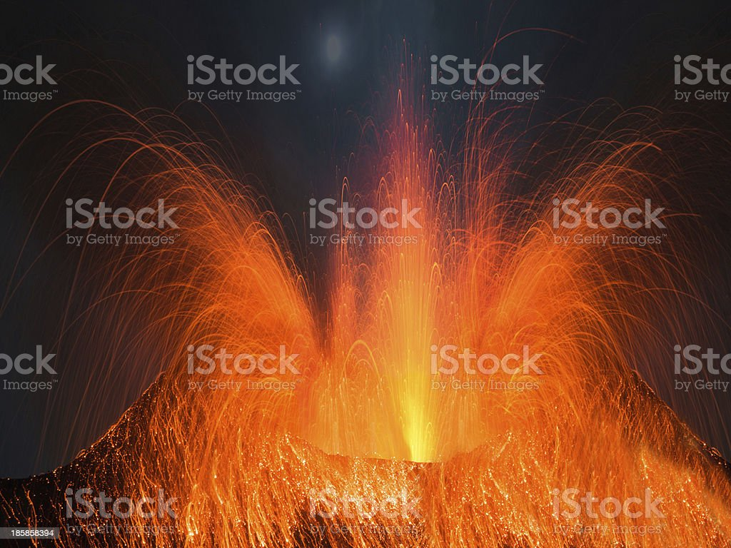 Volcano erupting at night stock photo