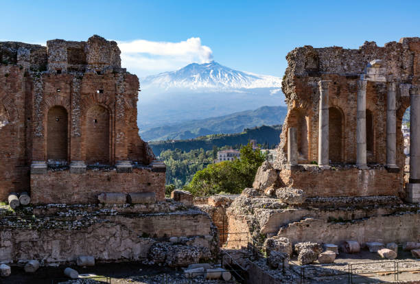 Volcano Etna in Sicily seen through ruins of ancient amphitheater in Taormina Two Sicilian landmarks on one photo sicily stock pictures, royalty-free photos & images