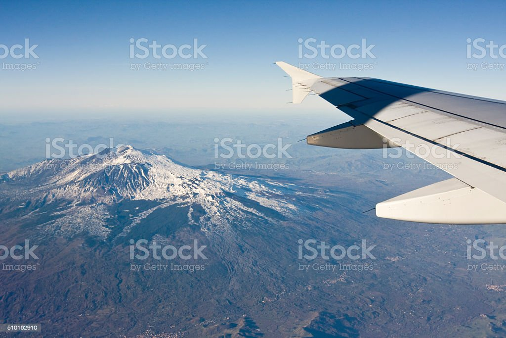 Volcano Etna view from Airbus A320 Airplane flying from Catania, Sicily to Rome, in the February morning. Aerial view on Etna volcano - highest European active stratovolcano. Due to winter snow visible on the mountain. Wing of an aircraft in the picture. Above Stock Photo
