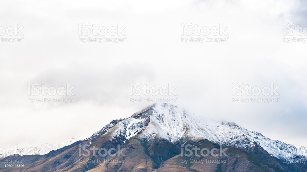 Volcano mountain covered with white snow. Foggy and cloudy. stock photo