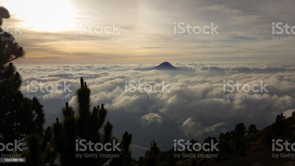Volcano over the clouds in Guatemala stock photo