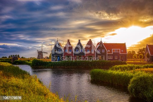 A traditional Dutch village with colorful, old wooden houses, vintage windmills and canals