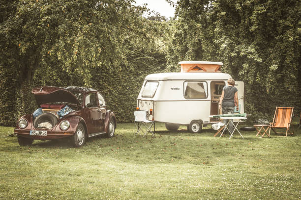 Volkswagen Beetle classic car with a caravan Volkswagen Beetle classic car  with a small caravan in a field with fruit trees. A woman is setting up the camping gear in front of the caravan. The car is on display during the 2016 Classic Days at Schloss Dyk in Juchen, Germany. caravan photos stock pictures, royalty-free photos & images