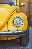 Sigtuna, Sweden - July 6, 2016: Front view of a yellow classic Volkswagen Beetle standing on parking lot. The beetle was produced by Volkswagen between 1938 and 2003.