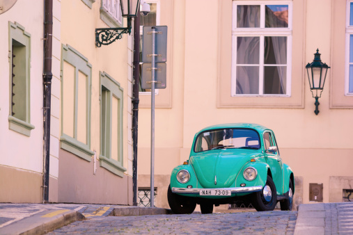 Prague, Czech Republic - August 17, 2013: A Volkswagen Beetle automobile is seen parked on the street next to a sidewalk in the Mala Strana neighborhood of Prague.