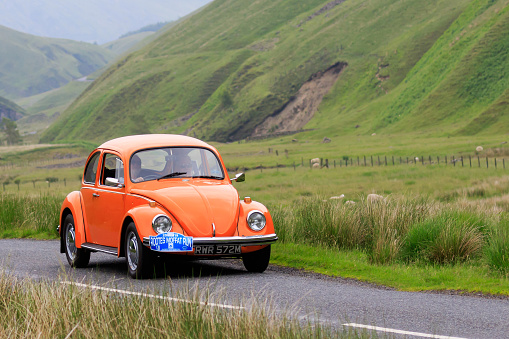 Moffat, Scotland - June 29, 2019: 1973 Volkswagen Beetle car in a classic car rally en route towards the town of Moffat, Dumfries and Galloway