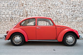 Valencia, Spain – September 01, 2012: Red Volkswagen Beetle parked in front of a stone wall on a street in Valencia.