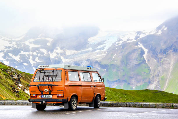 Volkswagen Caravelle Tyrol, Austria - July 29, 2014: Orange classic van Volkswagen Caravelle at the parking near the high Alpine mountain road. north rhine westphalia stock pictures, royalty-free photos & images