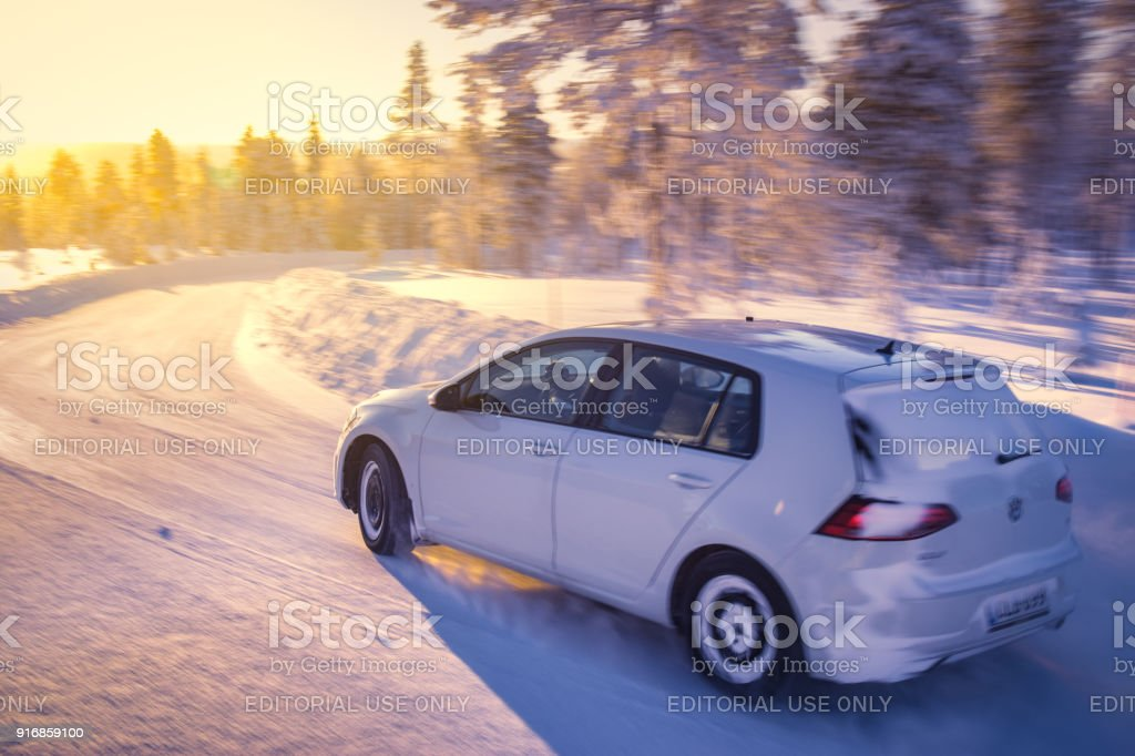 Volkswagen Golf drives on Lapland forest road stock photo