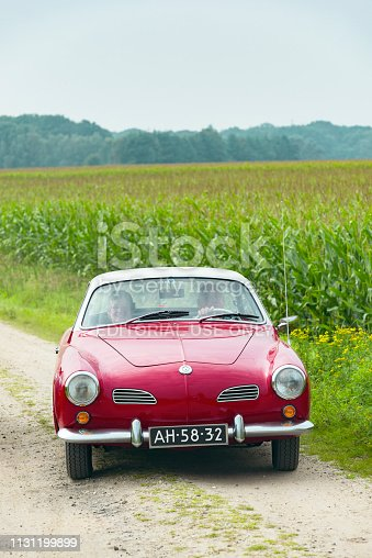 Volkswagen Karmann Ghia Type 14 driving on a country road in between corn fields near the village of Beekbergen in The Netherlands with people sitting inside the car.