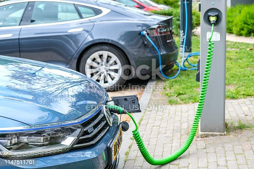 Volkswagen Passat GTE and Tesla Model S electric cars at an electric vehicle charging station in the city center of Zwolle, The Netherlands.