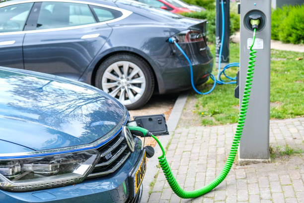 Volkswagen Passat GTE and Tesla Model S electric cars at an electric vehicle charging station stock photo