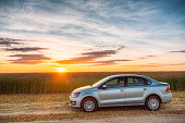 Volkswagen Polo Car Parking On Wheat Field. Sunset Sunrise Sky