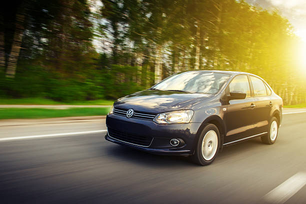Volkswagen Polo Sedan car drive on the road at sunset stock photo