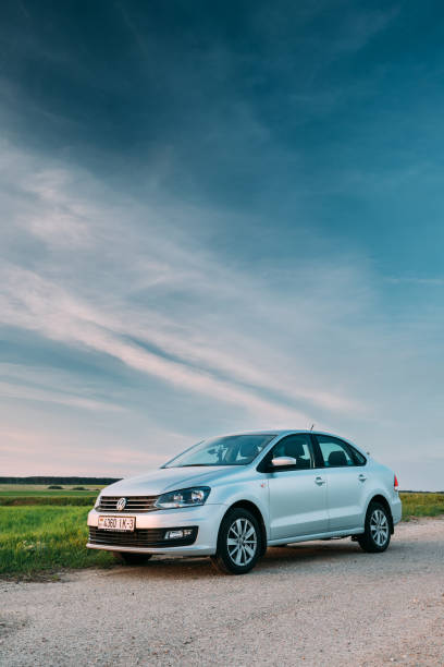 VW Volkswagen Polo Vento Sedan Car Parking In Field Near Country Road. Spring Or Summer Season. Wide Angle Shot stock photo