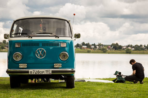 Volkswagen T1 transporter restored retro car on the lake. Man resting in nature stock photo