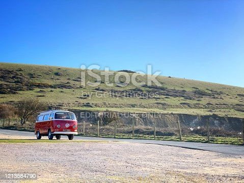 Alum Bay, Isle of Wight, England - March 16, 2020: A red Volkswagen T2 Campervan parks at an empty car park at The Needles Landmark Attraction during Coronavirus pandemic