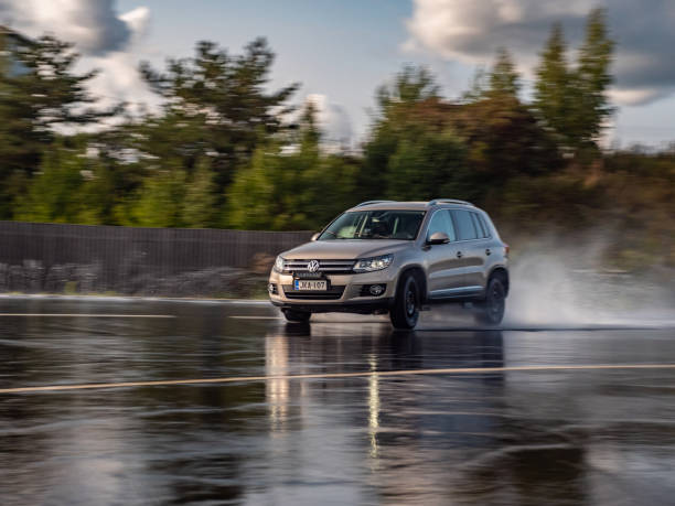 Volkswagen Tiguan drives on a slippery wet road. stock photo