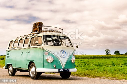 Beekbergen, The Netherlands - September 6, 2015: 1950s Volkswagen Samba or Sunroof Deluxe classic car. Two people are sitting inside the VW that is driving on a country road.