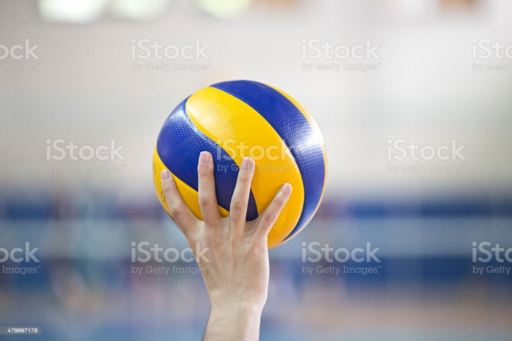 Holding a volley ball during the match.