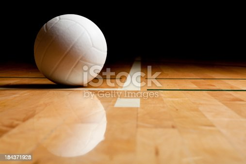 A white volleyball on the floor in a darkened gym.