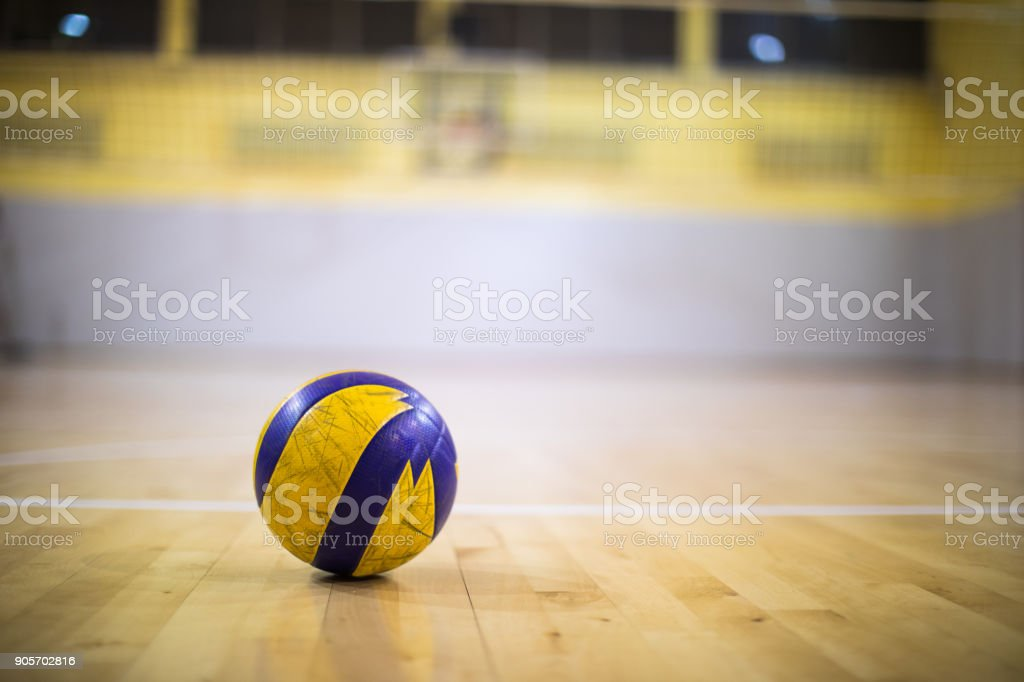 A yellow-blue volleyball ball on a wooden gym floor