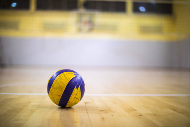 a volleyball ball on a wooden gym floor - volleyball stock photos and pictures