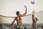 Young friends having fun while playing volleyball on the beach. Man is blocking his friend.