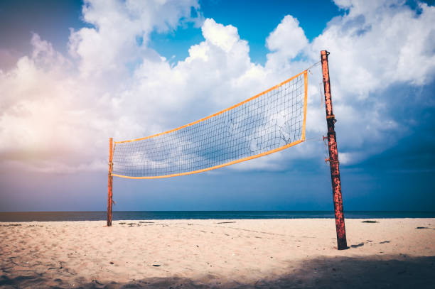 Volleyball court on an empty beach with blue cloudy sky. stock photo