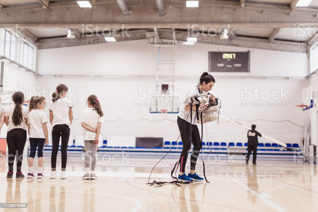 Volleyball female coach removing volleyball net after training on...