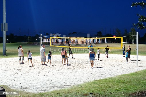 Royal Palm Beach, USA - November 7, 2015: Adults and children play a pick up game of volleyball under the lights at a public park. The volleyball net is set up on a large sand court. Night shot under artificial lighting. Social gathering of families in a public park.