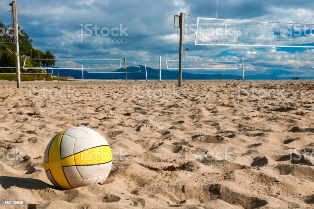 Volleyball in Close Foreground Sits on Beach with Nets and Courts Beyond – zdjęcie
