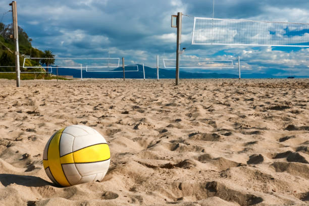 Volleyball in Close Foreground Sits on Beach with Nets and Courts Beyond stock photo